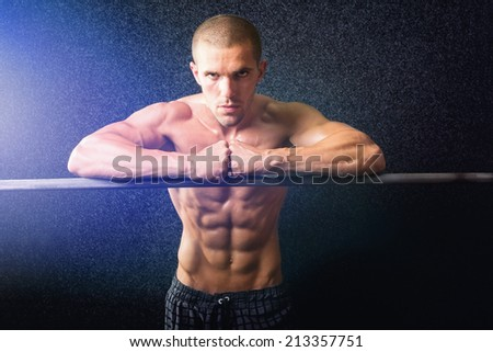 Handsome shirtless fitness young Caucasian man in gym. Muscular guy posing against dark background. Fitness and bodybuilding concepts. - stock photo