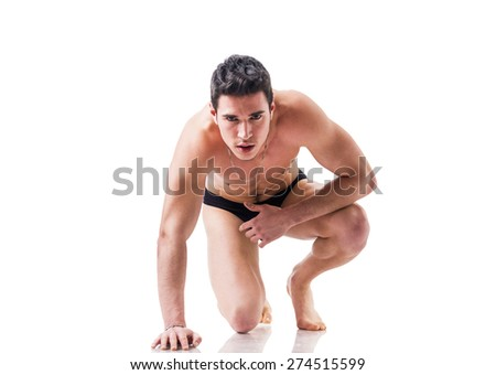Handsome shirtless guy wearing black underwear, ready for a sprint isolated in white - stock photo