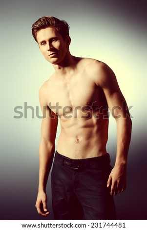 Handsome shirtless male model posing at studio. Men's beauty, healthcare.