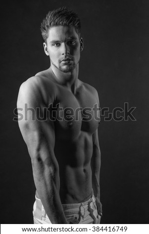 Handsome shirtless male model standing against a black background with six pack abs - A healthy young man  - stock photo