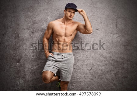 Handsome shirtless man leaning against a rusty gray wall and looking at the camera