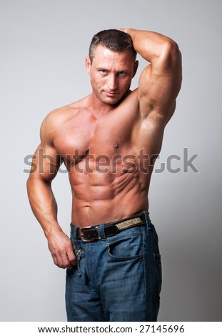Handsome shirtless man on gray background