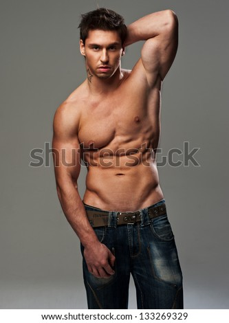 Handsome shirtless man with hands behind his head