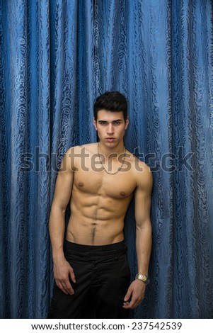 Handsome shirtless muscular young man, looking at camera, standing against blue curtains - stock photo