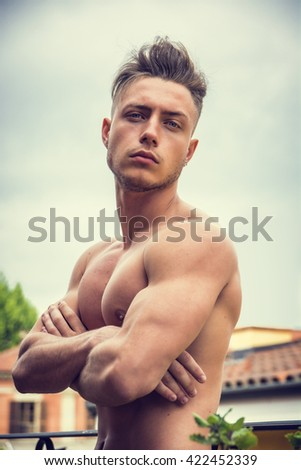 Handsome shirtless muscular young man outdoor, looking at camera, arms crossed on chest - stock photo