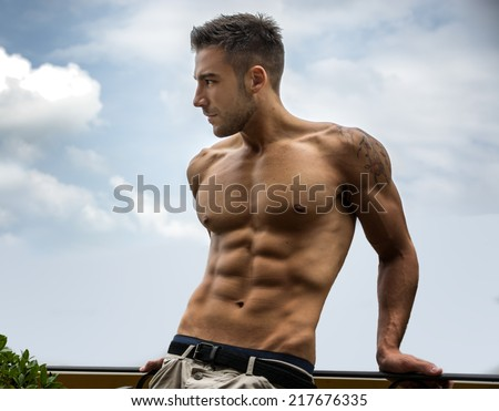 Handsome shirtless muscular young man outdoor, looking away - stock photo