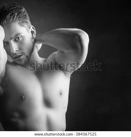 Handsome shirtless sexy male model against a black background. Muscular torso and six pack abs. - stock photo