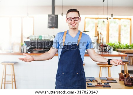 handsome shop owner inviting to his shop - stock photo