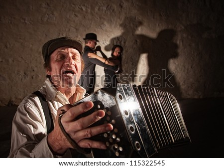 Handsome singer playing accordion with tango dancers in background