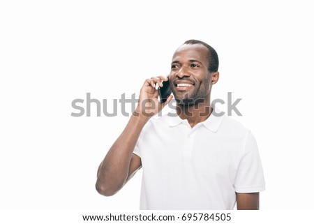 handsome smiling african american man talking on smartphone isolated on white