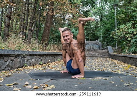 Handsome smiling Athletic flexible man doing yoga asanas in the park in the fall