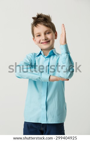 Handsome smiling boy in blue shirt and jeans standing with hand up - stock photo