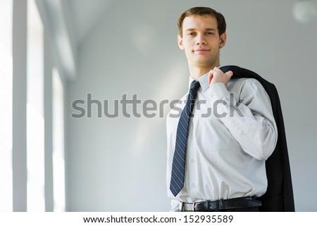 Handsome smiling businessman holding jacket on his shoulder - stock photo
