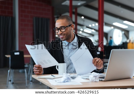Handsome smiling businessman looking at documents and listens to music  - stock photo