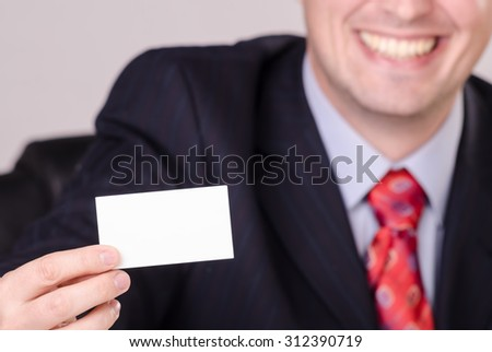 Handsome smiling businessman showing business card with space for your text. - stock photo