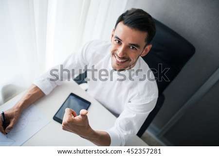 Handsome smiling businessman working with a device, gadget in the office, sitting on the chair and look at the camera and going thumbs up. Business.View from above - stock photo