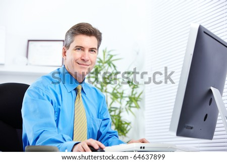 Handsome smiling businessman working with computer.