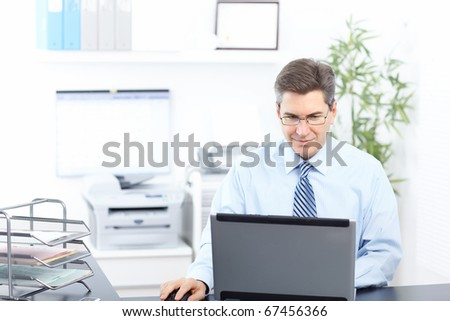 Handsome smiling businessman working with laptop. - stock photo