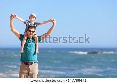 handsome smiling father and his happy son sitting on shoulders holding hands at the beach