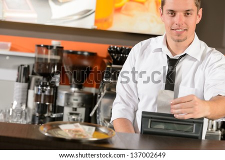 Handsome smiling male waiter giving receipt czech crowns in pub - stock photo