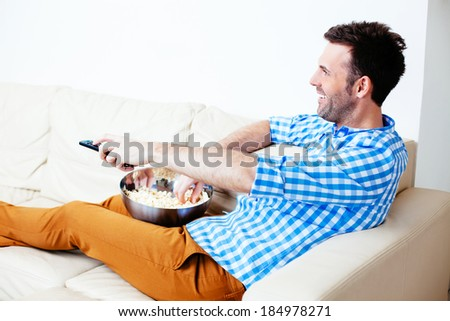Handsome smiling man channel hopping on a sofa - stock photo