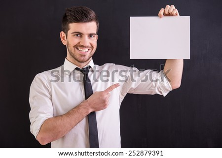 Handsome, smiling man is holding white blank while standing on the dark background. - stock photo