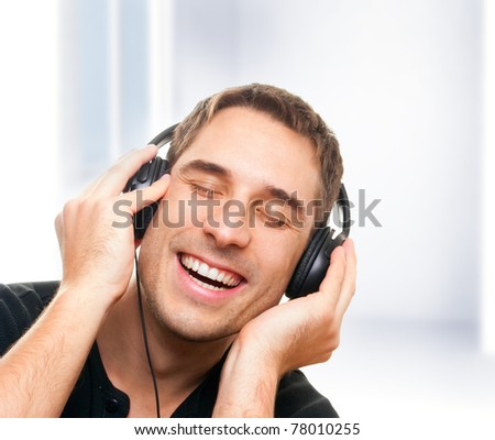 handsome smiling man listening the music. - stock photo