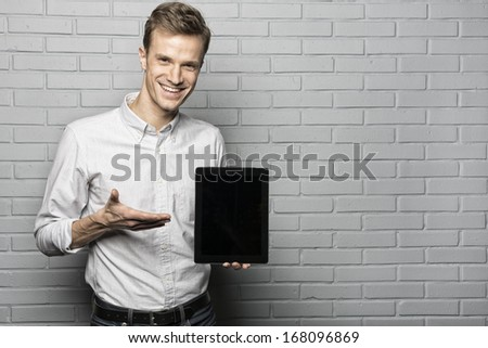 Handsome smiling man standing on Grey wall background,With Tablet Pc, Looking camera - stock photo