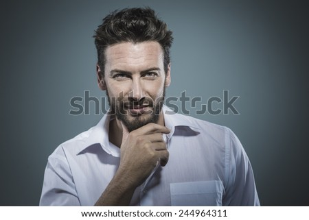 Handsome smiling man with hand on chin posing - stock photo