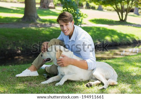 Handsome smiling man with his labrador in the park on a sunny day - stock photo