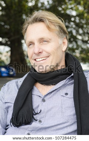 handsome smiling mature blond man wearing a blue shirt and black tie while sitting down in a park. - stock photo