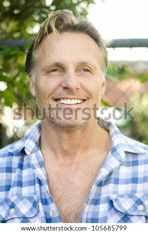handsome smiling mature blond man with stubble wearing a blue checked shirt. - stock photo