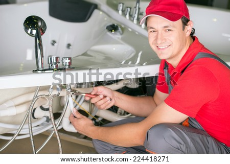Handsome smiling plumber at the bathroom. Reparation. - stock photo