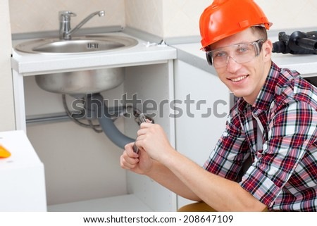 Handsome smiling plumber at the kitchen - stock photo