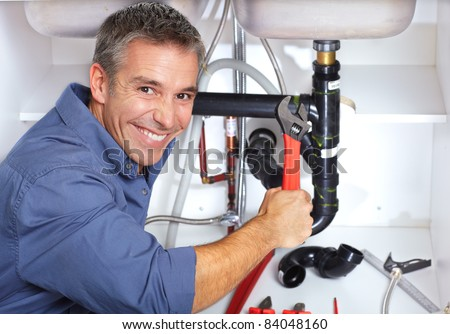 Handsome smiling plumber at the kitchen. Reparation. - stock photo