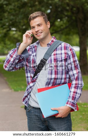 Handsome smiling student standing and phoning on campus at college - stock photo