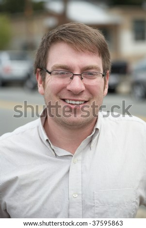 Handsome smiling student with glasses outdoor portrait headshot - stock photo