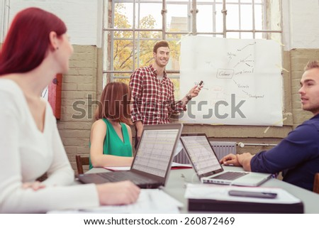 Handsome smiling team leader giving a presentation to his team pointing to a hand drawn graph as they sit around a table watching and following on their laptops - stock photo