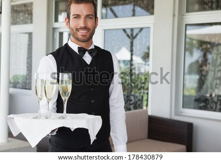 Handsome smiling waiter holding tray of champagne in the patio of restaurant - stock photo