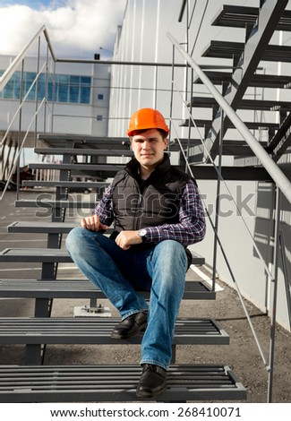 Handsome smiling worker relaxing on metal staircase during break