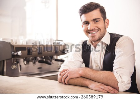 Handsome smiling young barista in his caf���©. - stock photo