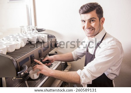 Handsome smiling young barista is making coffee in his cafe. - stock photo
