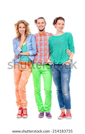 Handsome smiling young man stands between two beautiful girls. Isolated over white.