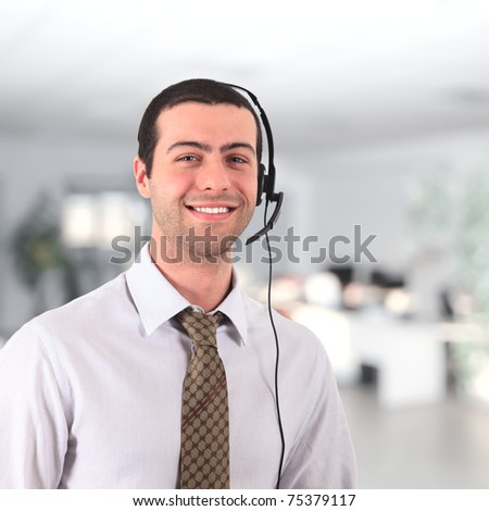 Handsome smiling young man wearing an headset - stock photo