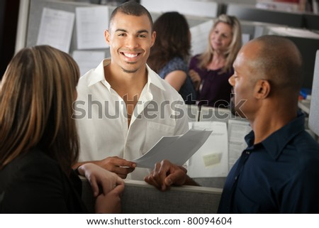 Handsome smiling young office employee with co-workers