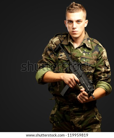 handsome soldier holding gun against a black background - stock photo