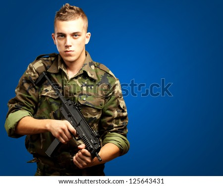handsome soldier holding gun against a blue background - stock photo