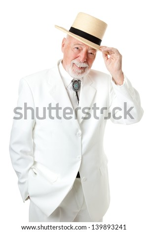 Handsome Southern senior man tipping his hat, with old fashioned chivalry.  Isolated on white. - stock photo