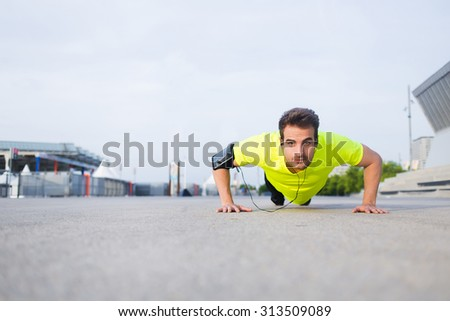 Handsome sports man with running armband doing push-ups on asphalt city road while listening to music with headphones,caucasian male jogger warm up before start his workout training outside in morning - stock photo