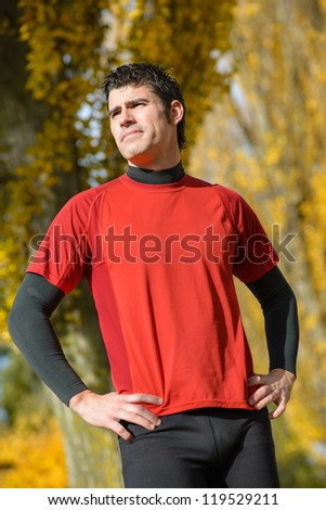 Handsome sportsman in heroic pose. Standing male athlete looking with determination attitude. - stock photo